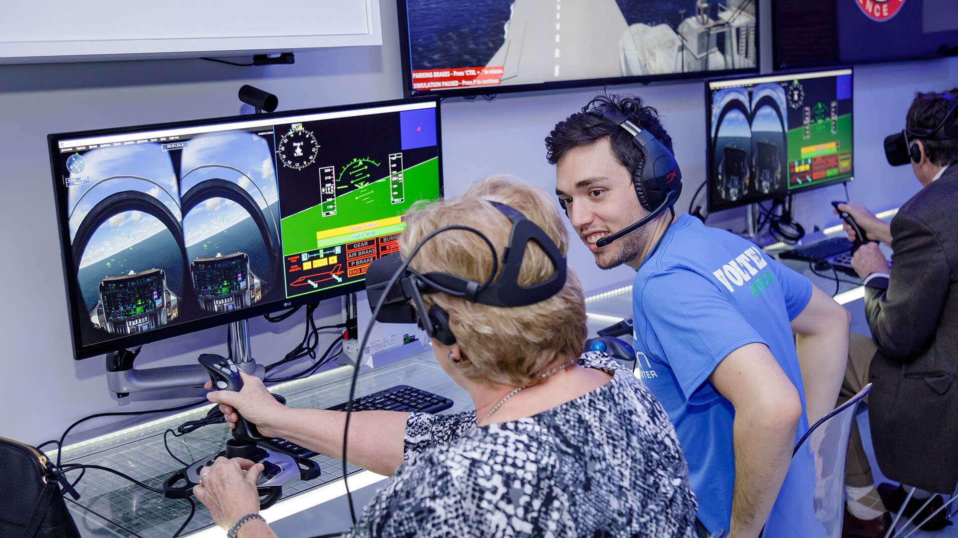 Adult volunteer in the Flight Lab exhibit assisting guest.