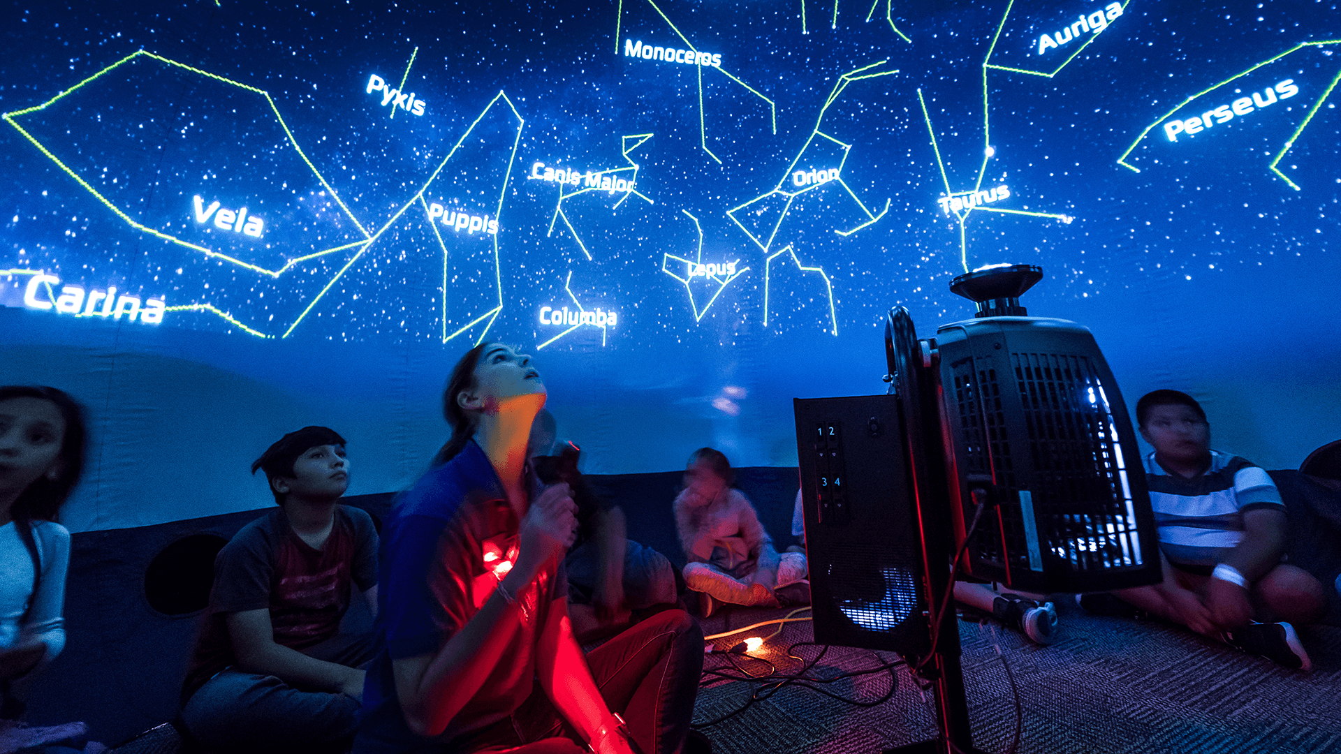 A group of children watch a presentation in the mobile planetarium as part of offerings for educators and students.