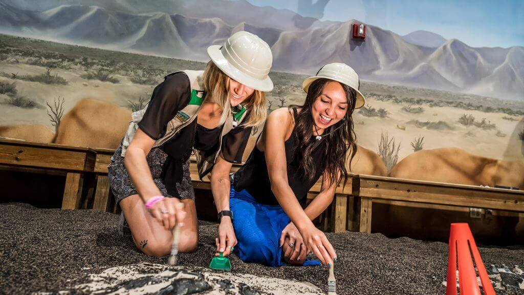Adults laughing and digging for fossils in the DinoDigs exhibit.