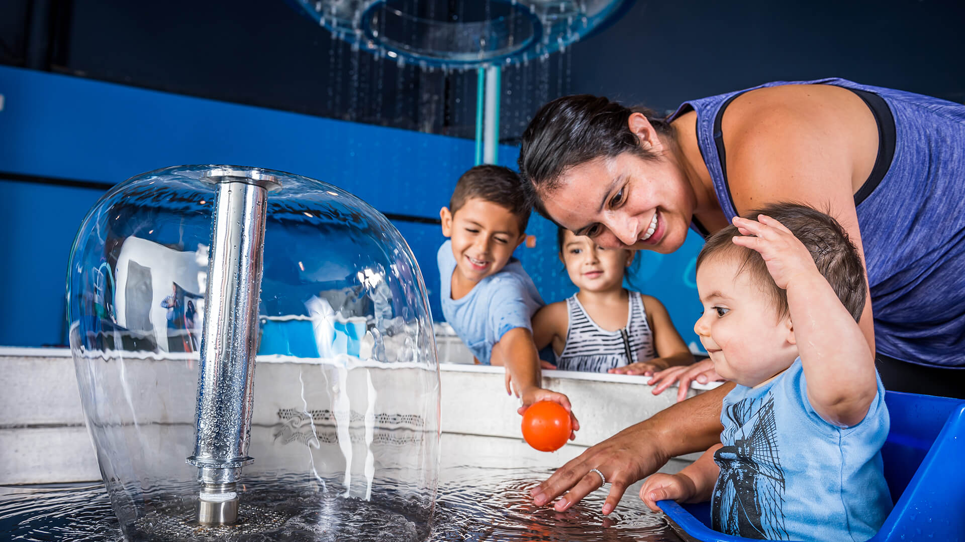 A mother and her children splash in the water play area of the KidsTown exhibit.