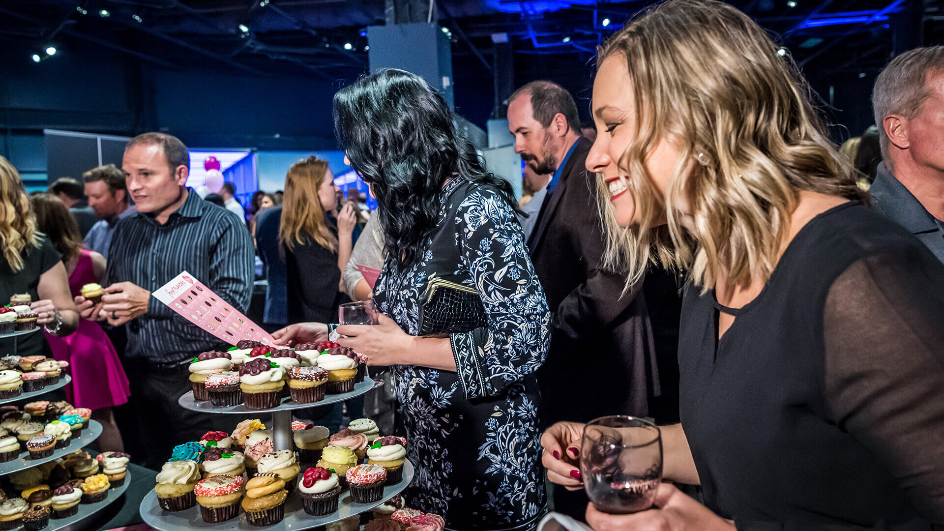 Guests picking up cupcakes at a food table.