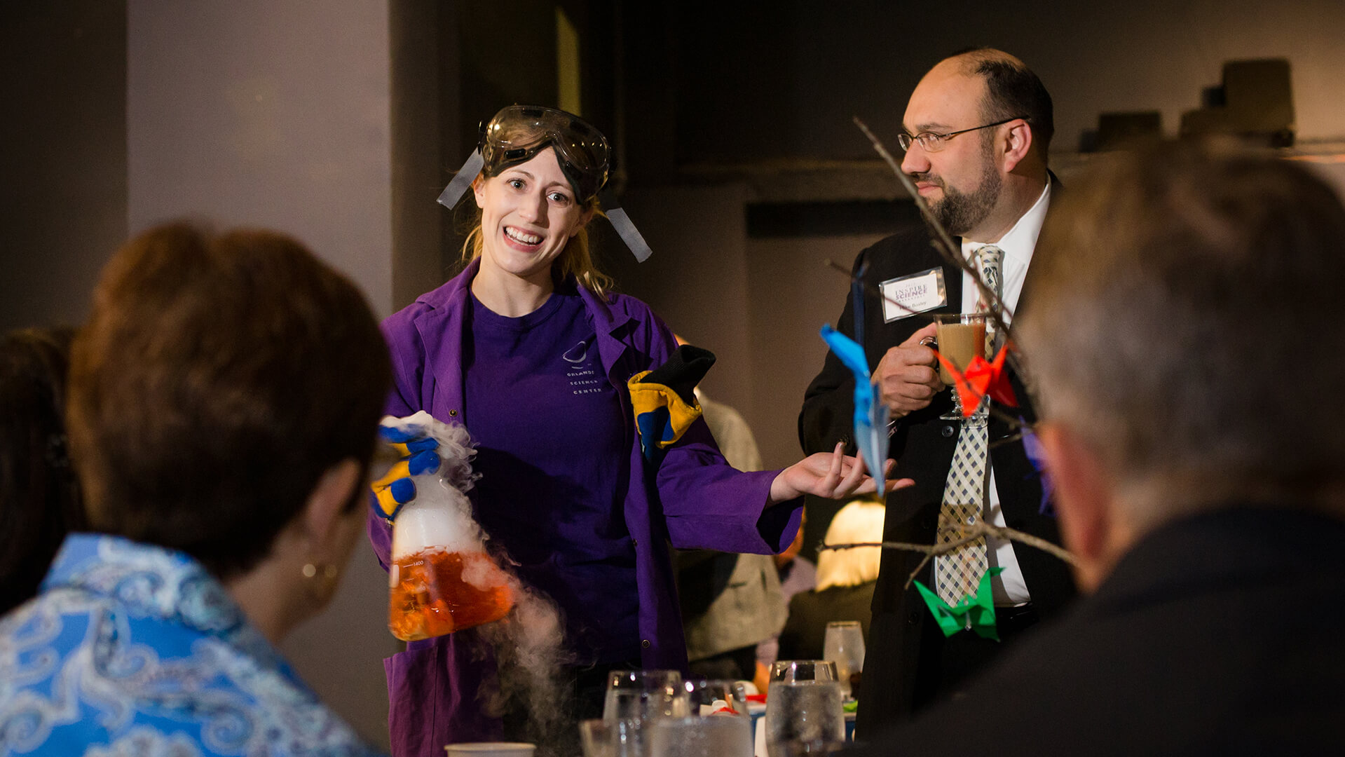 A Science Center presenter shows a beaker of liquid nitrogen to some guests.