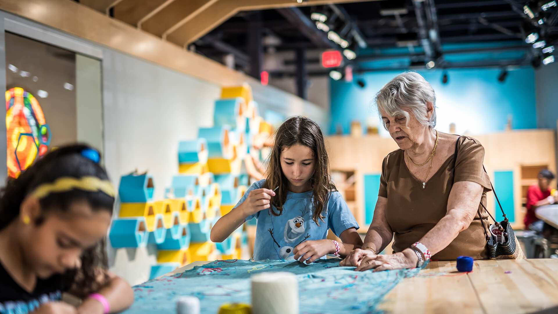 A grandmother and child practice sewing together in The Hive: A Makerspace.