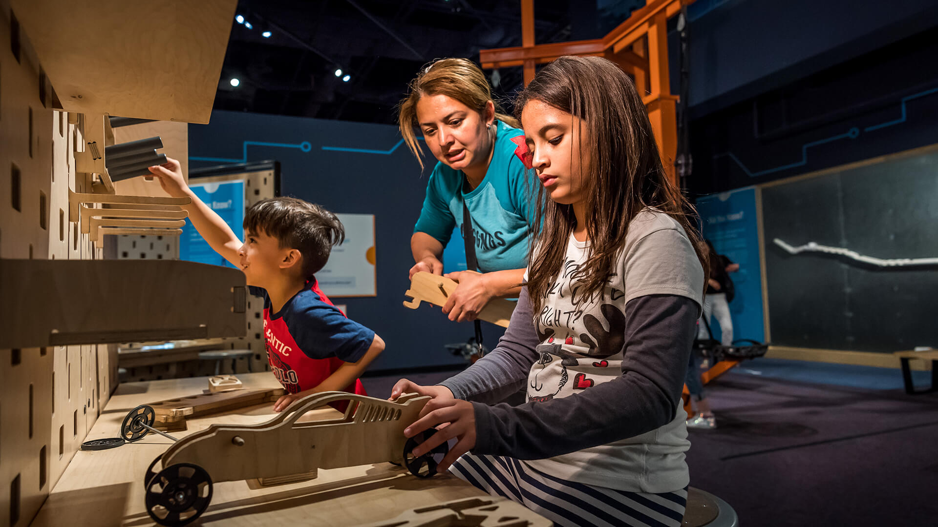 A family builds model cars in the Kinetic Zone exhibit.