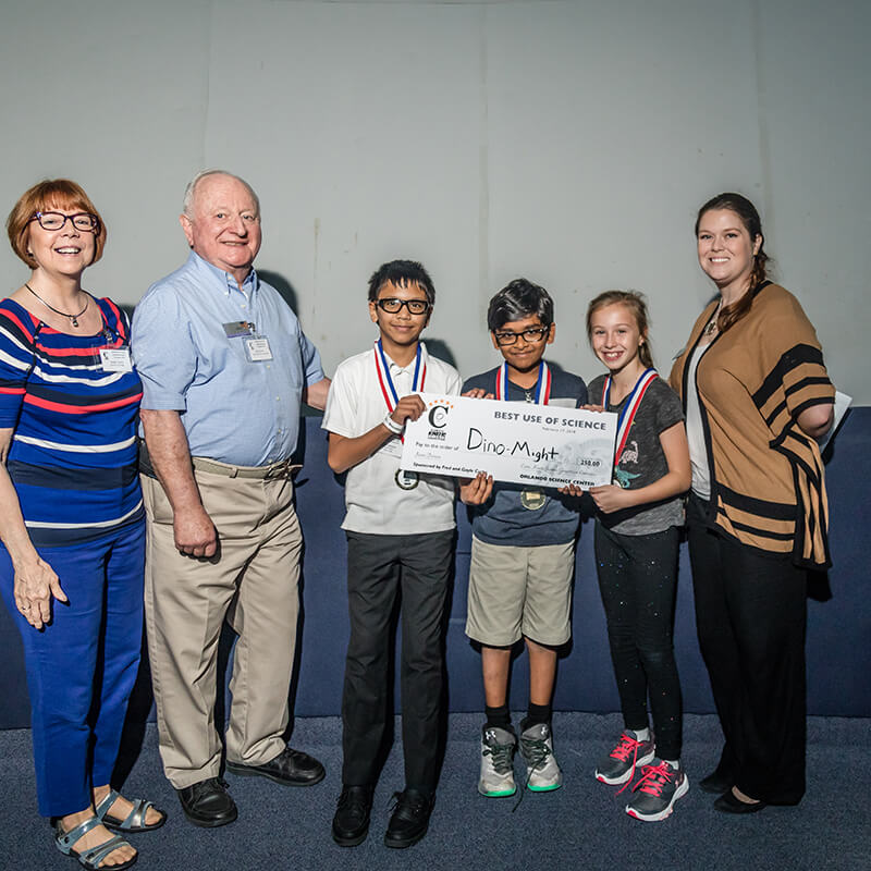Students posing with their giant check prize at the Curtis Kinetic Science Competition.