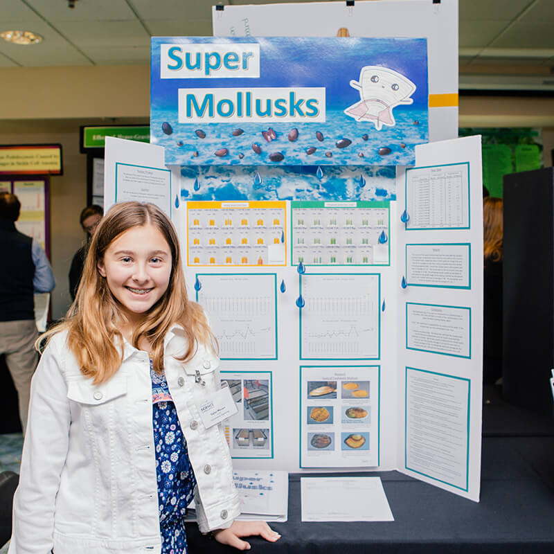 A middle schooler posing with her mollusk research project.