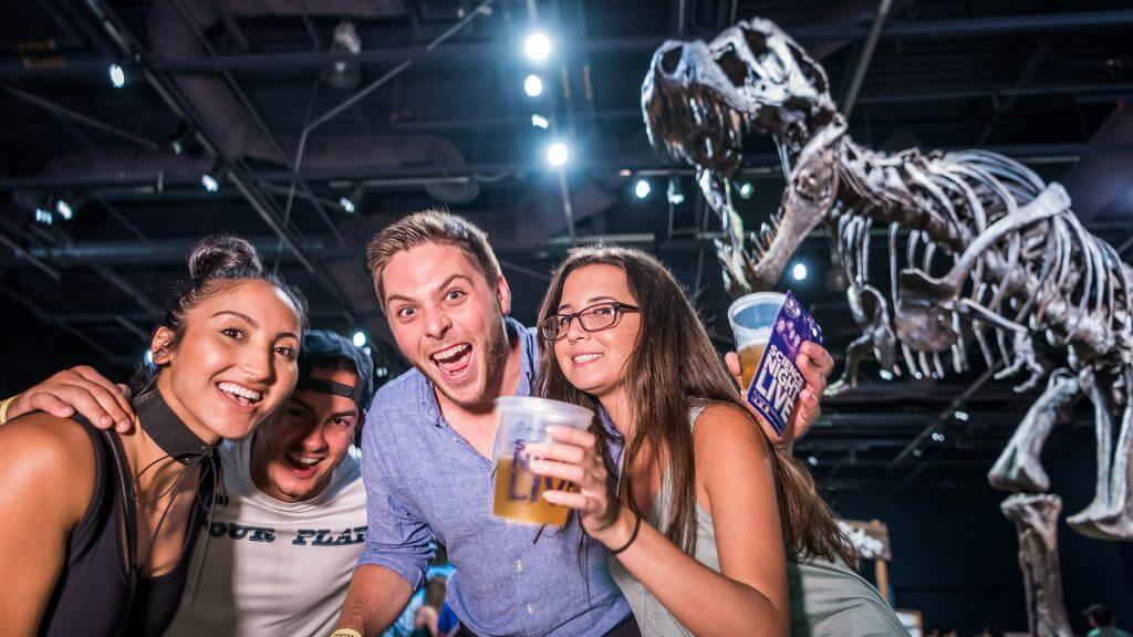 A group of friends with drinks posing under the T. Rex.
