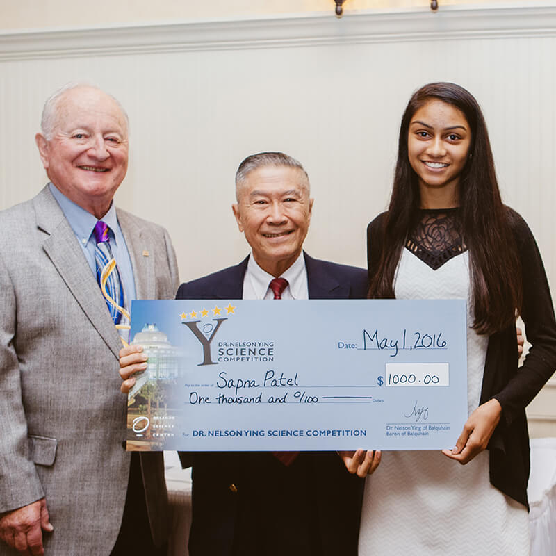 Dr. Ying presents a giant check award to a winning student.