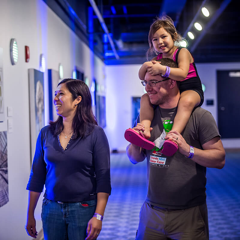 A family walking through the Fusion art gallery.