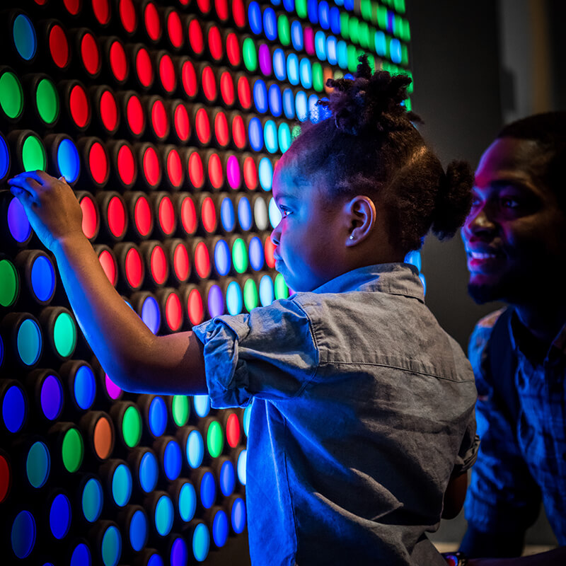 A girl changes the colors on panels of the giant Lite Brite.