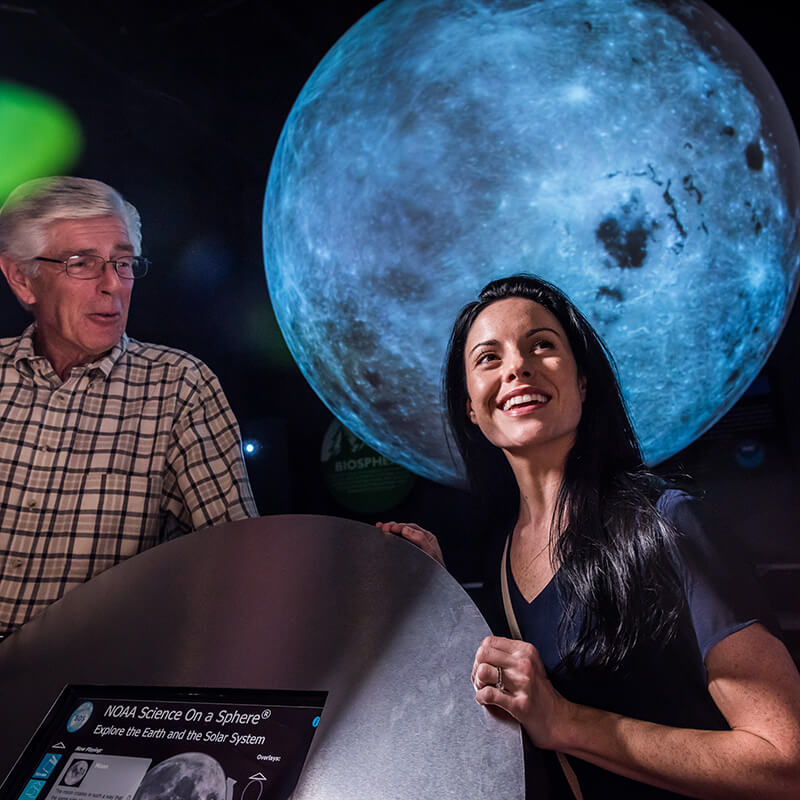 A woman and her father look at a model of the moon with Science on a Sphere.