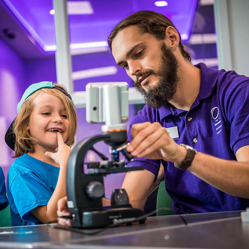 Instructor demonstrates how to use a microscope to a young kid