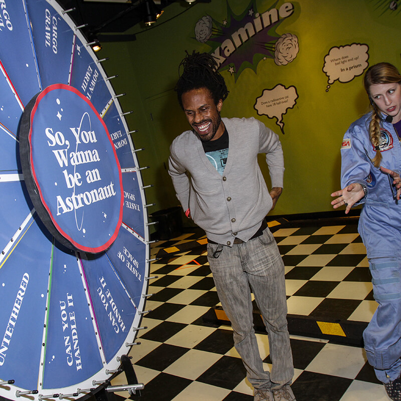 A guest spins a prize wheel during an astronaut live show.