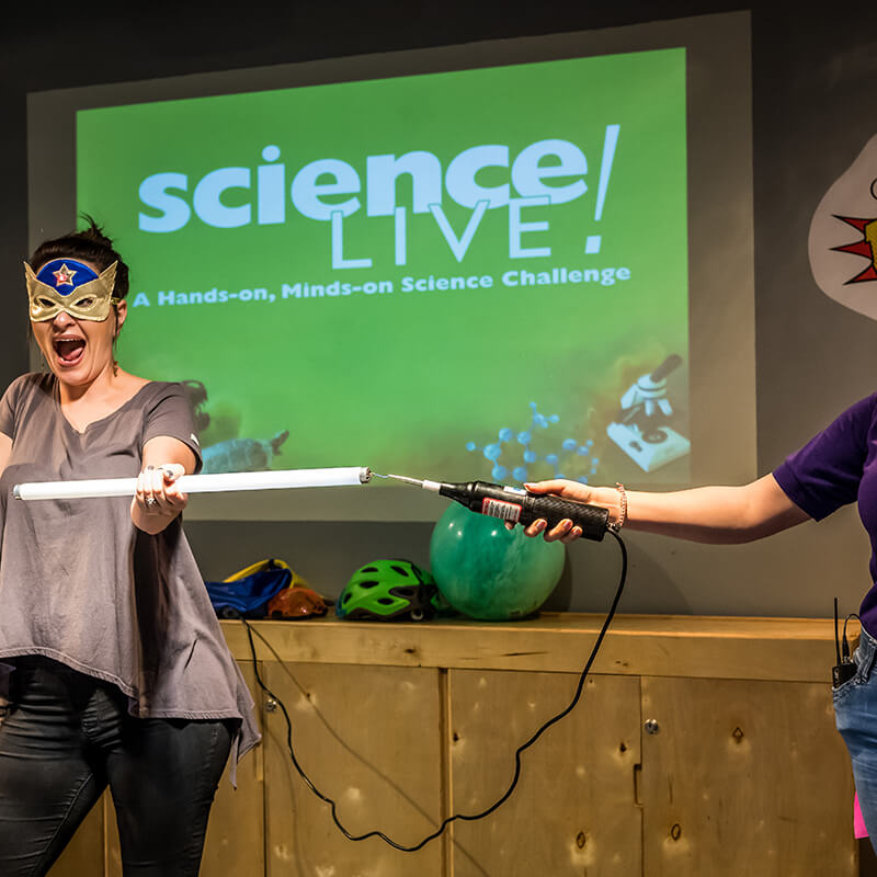 A woman holds a large light bulb during a Science Live! show.