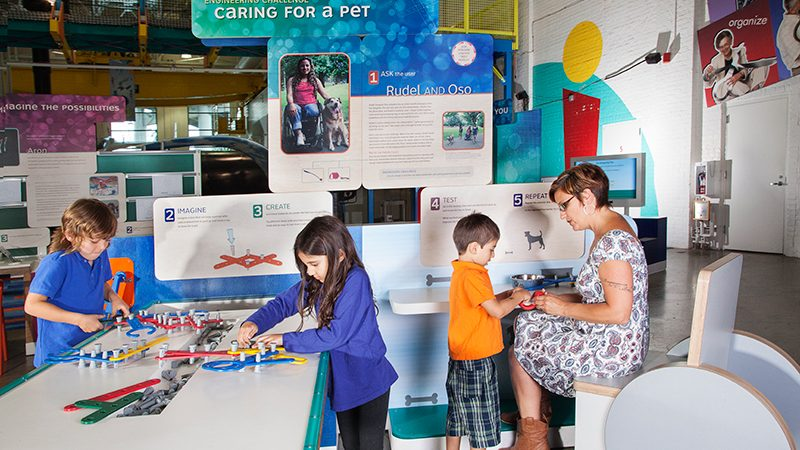 A family building tools to help a person who uses a wheelchair pick up a pet food bowl.
