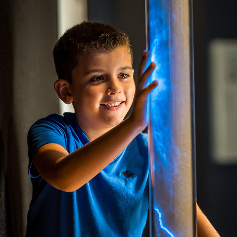 A boy attracting blue light to his hand with the lightning tube.