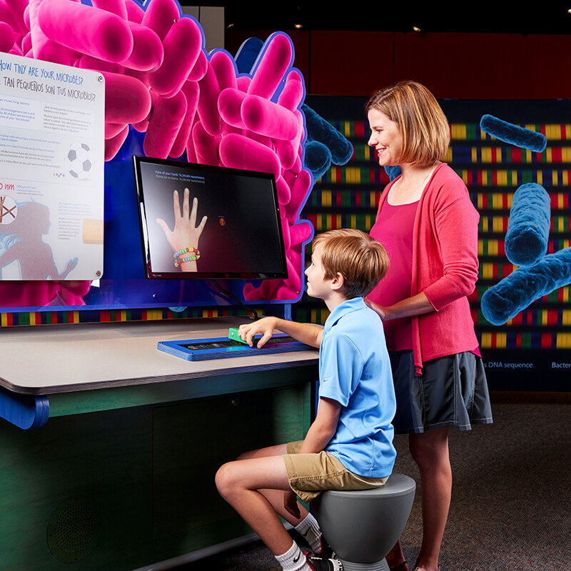 A mother and her son looking at a computer and learning about microbes.