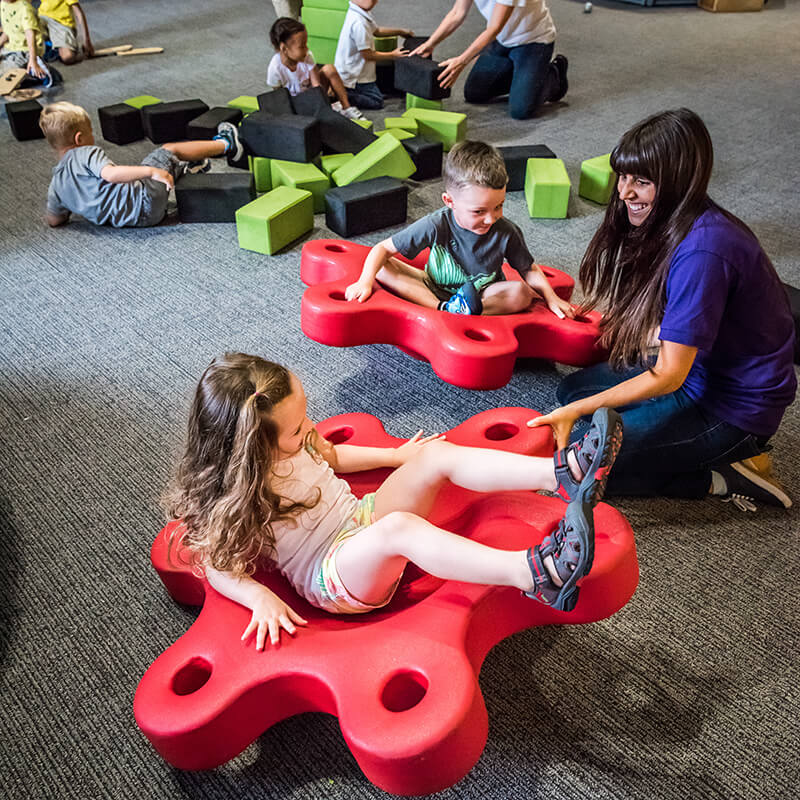 An employee spins children on flower-shaped rocking seats.