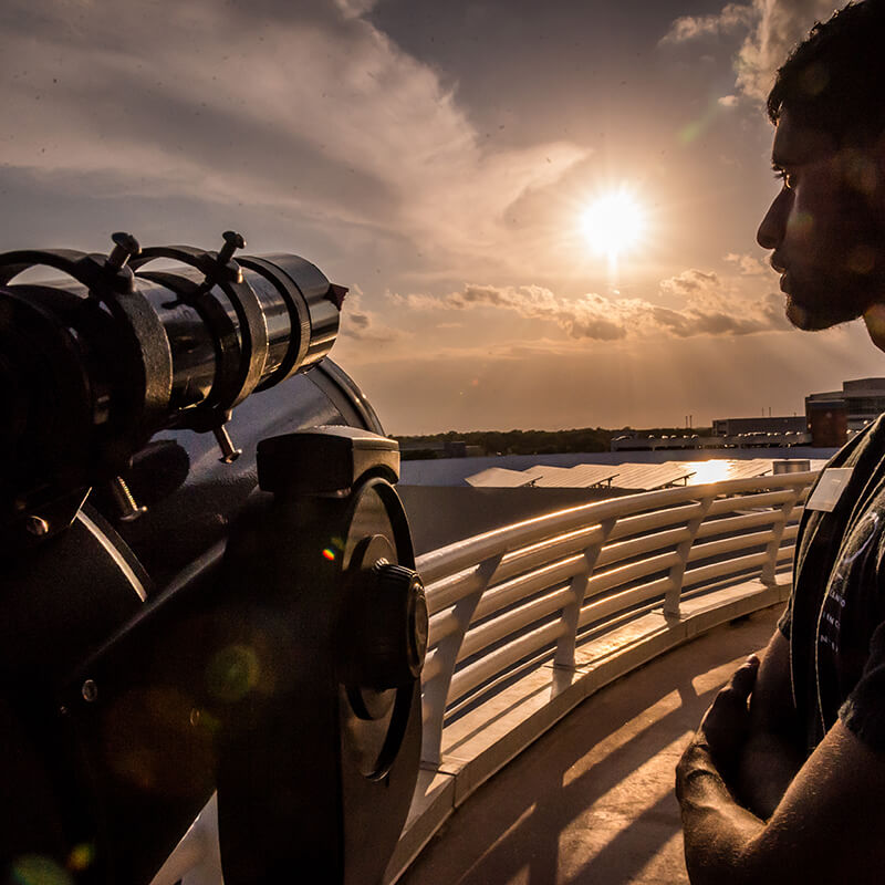 A man looking at a telescope outside at sunset.