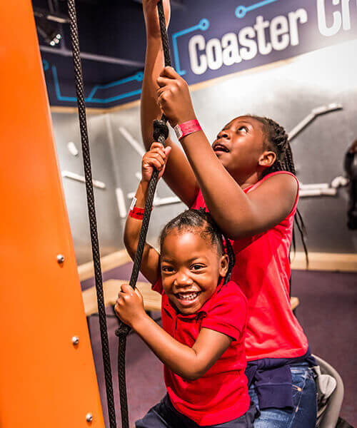 Two kids pulling on a rope as part of an exhibit