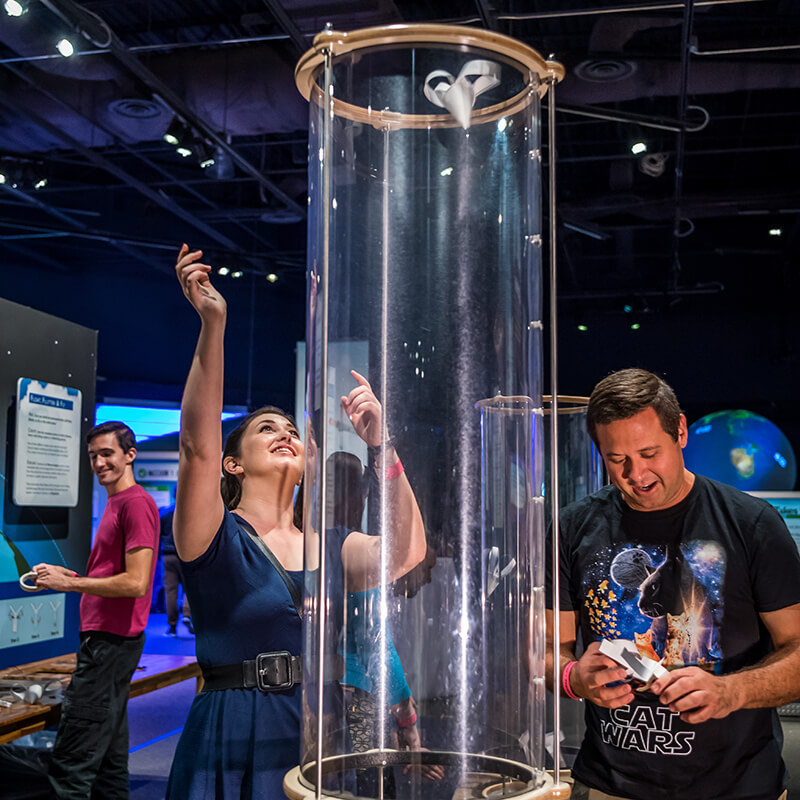 A couple tests their weather instrument models in a wind tube.
