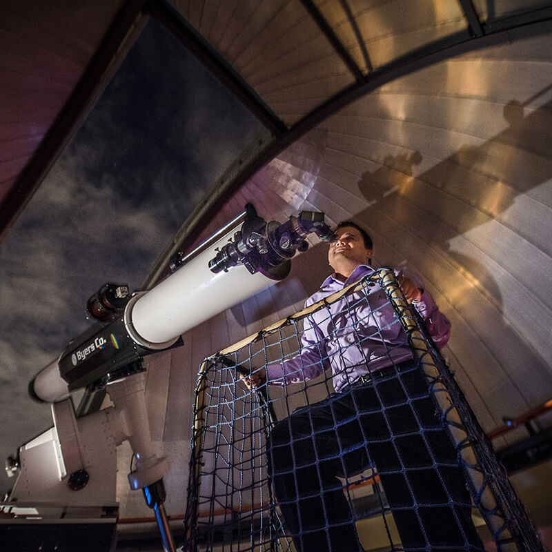 A man looking through the refractor telescope in the observatory.