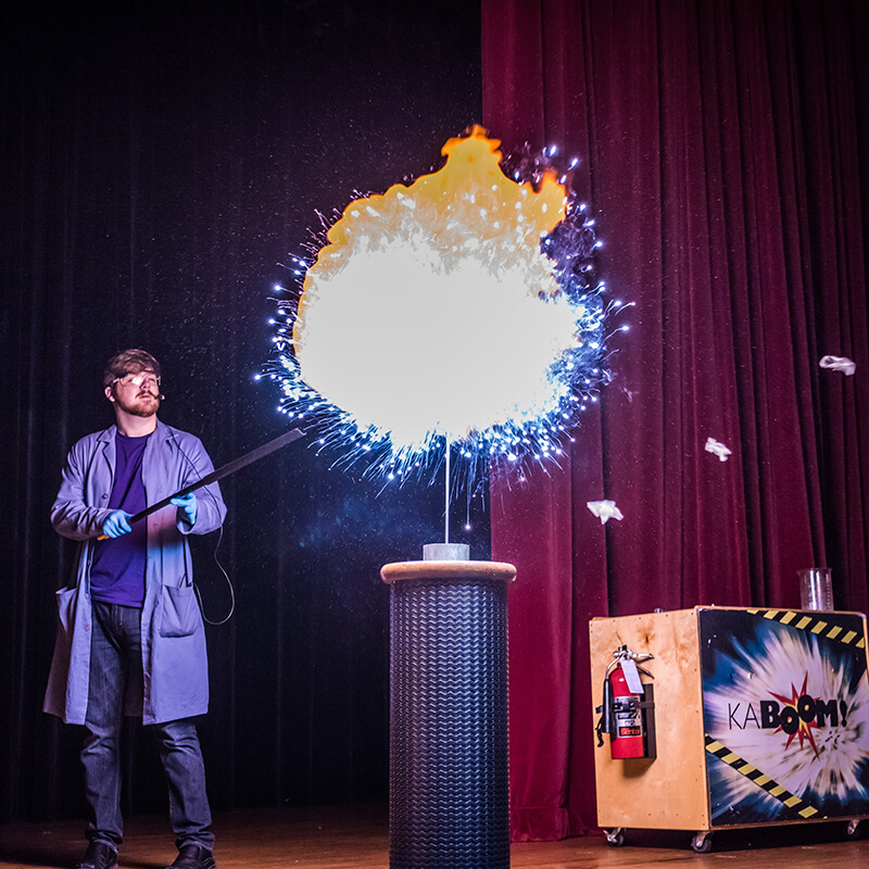 A presenter makes a hydrogen balloon explode into an illuminated display.