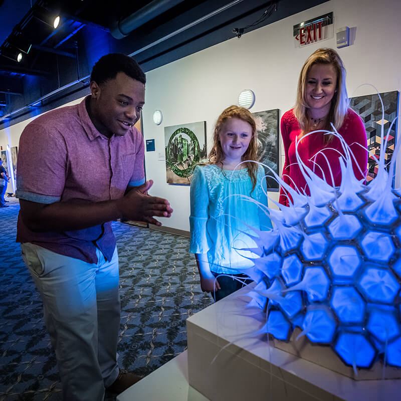 Guests reacting to a sculpture of a microorganism.