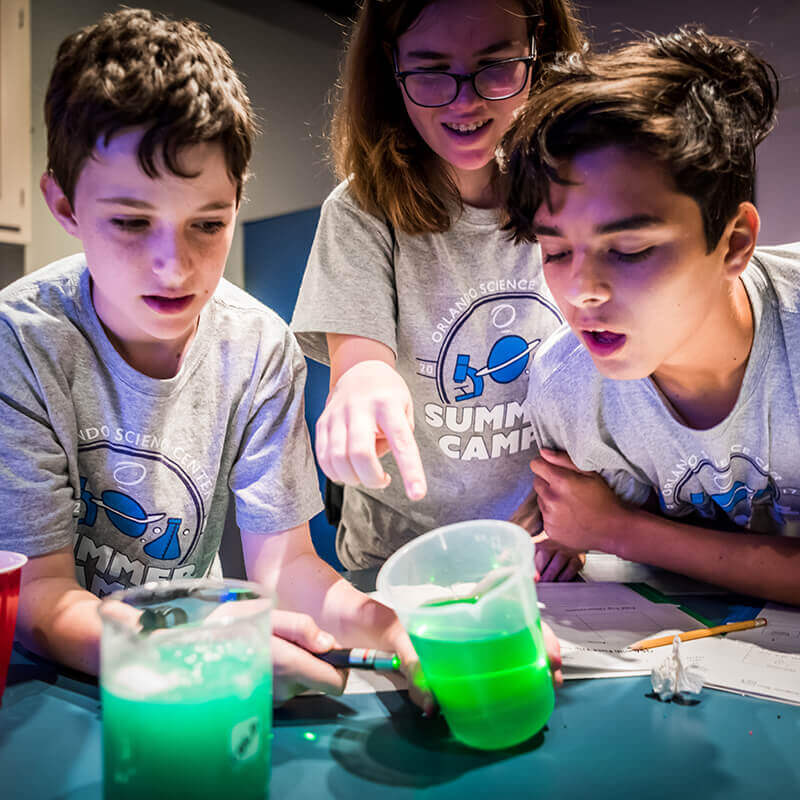 Group of kids looking at beakers full of green solution
