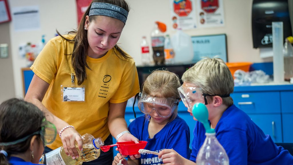 Youth volunteer helping summer camp students measure ingredients for an experiment.