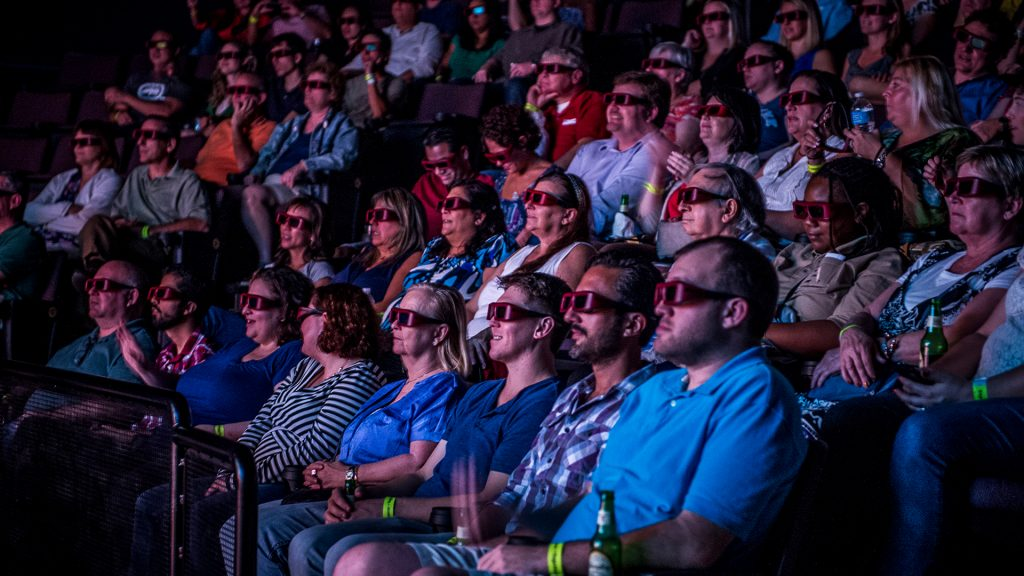 Crowd wearing 3D glasses watches a Hollywood film in the Digital Adventure Theater.
