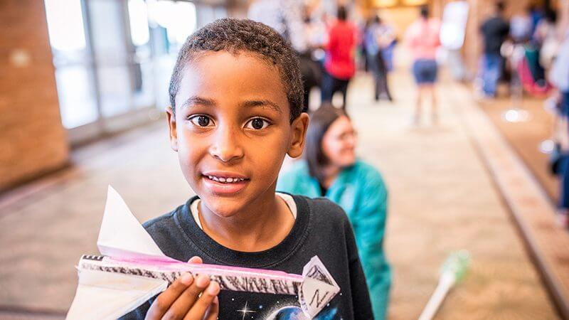 Child in afterschool program holding a paper rocket that he made.