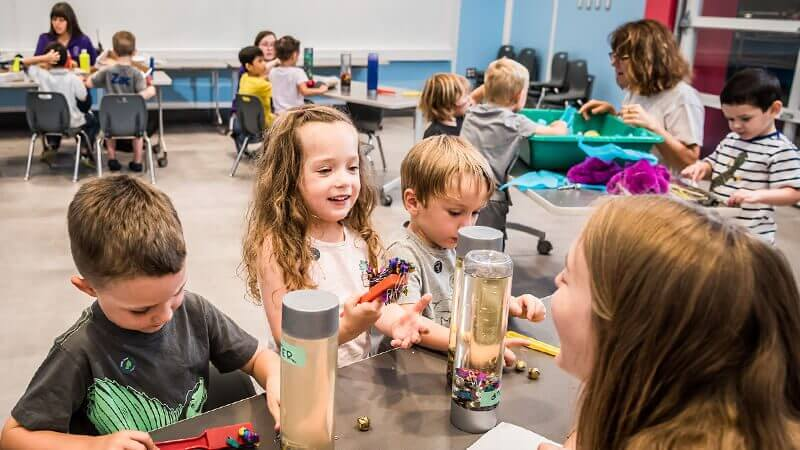 An educator shows preschoolers how to use magnet bars to pick up objects.
