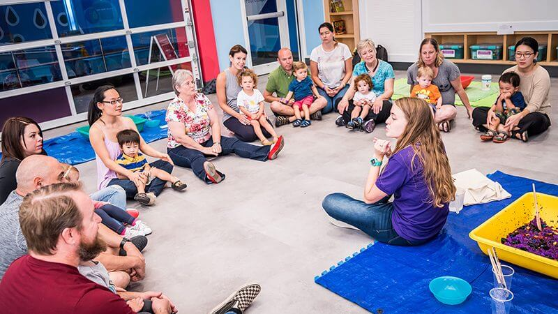 A group of toddlers and caretakers sit in a circle and listen to an educator during the Little Explorers program.