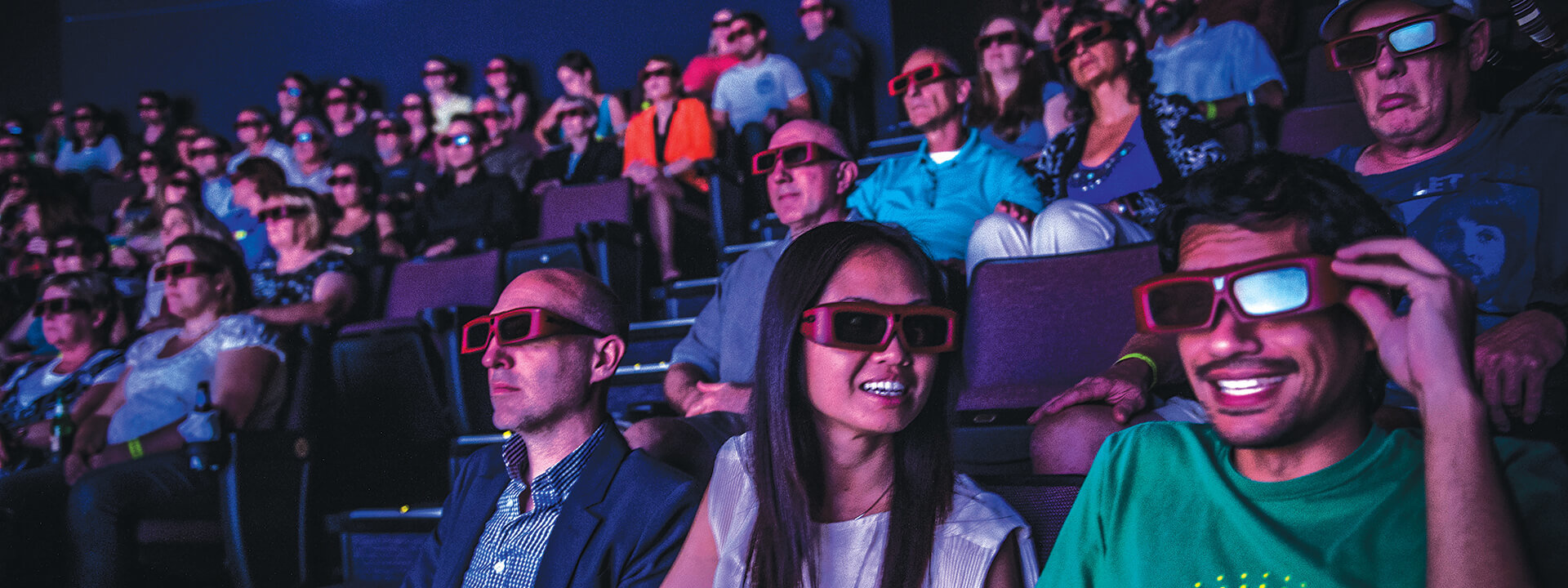 Crowd of guests in theater wearing 3D glasses enjoying a movie.