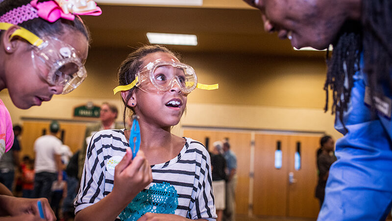 Girl wearing lab goggles doing a science experiment in the afterschool program.