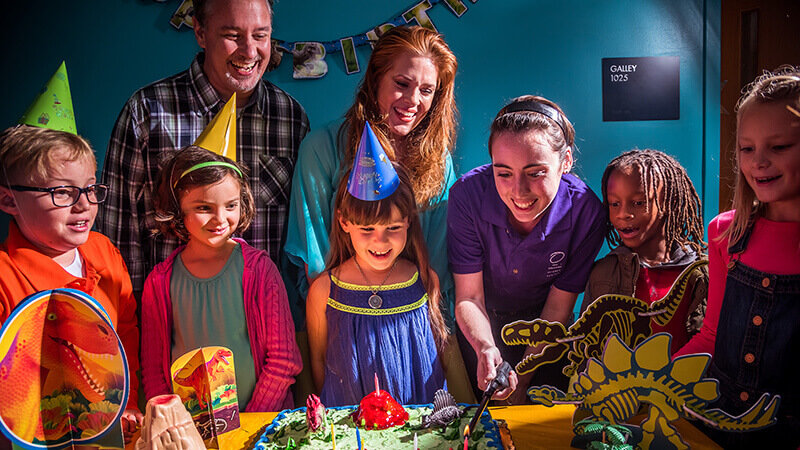 Family and friends lighting candles on a birthday cake.
