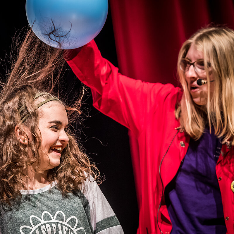 A presenter uses static on a balloon to make a girl's hair stand up.