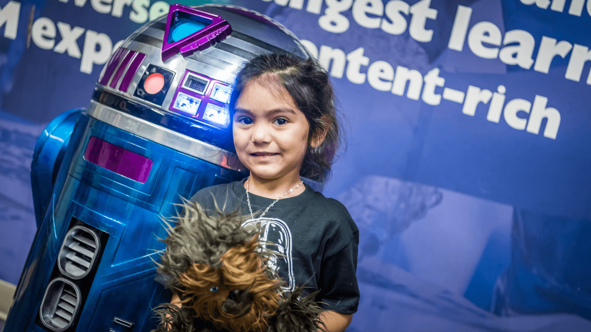 Girl holding a Chewbacca toy standing next to a droid