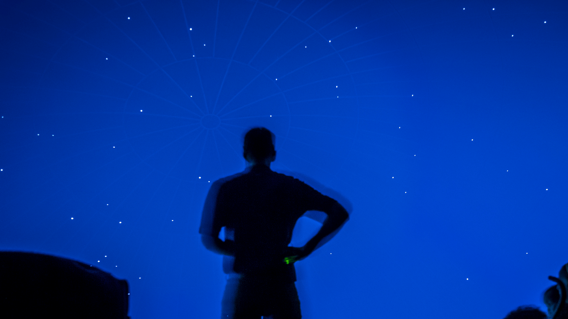 silhouette of a man standing in front of observatory