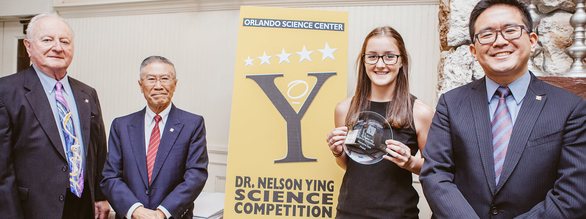 A high school student smiles with her award at the Dr. Nelson Ying Science Competition.