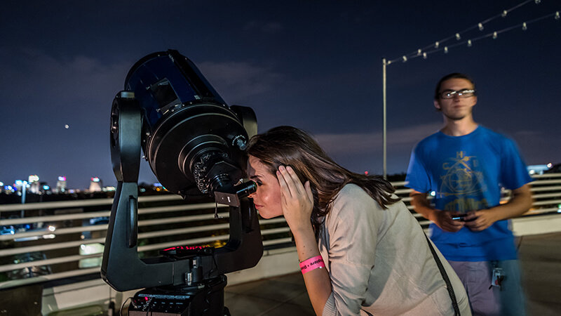 A guest looking through a telescope at night outside.
