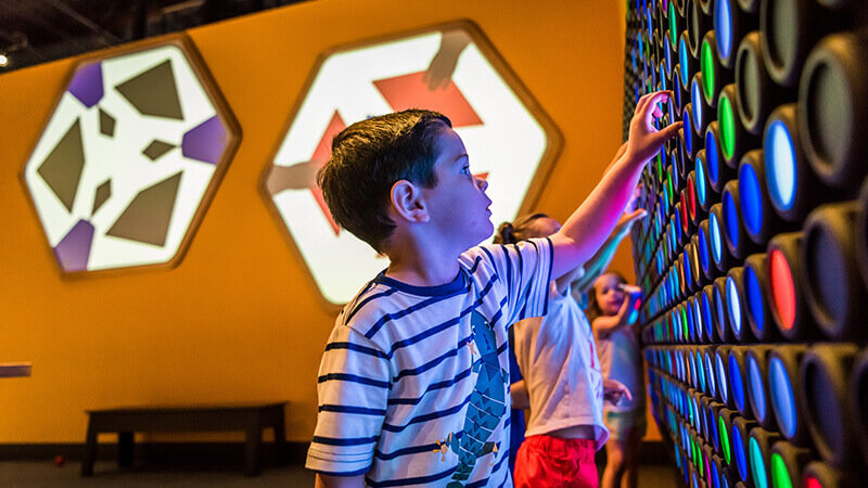 A child rotates multicolored panels on the wall to make a design.