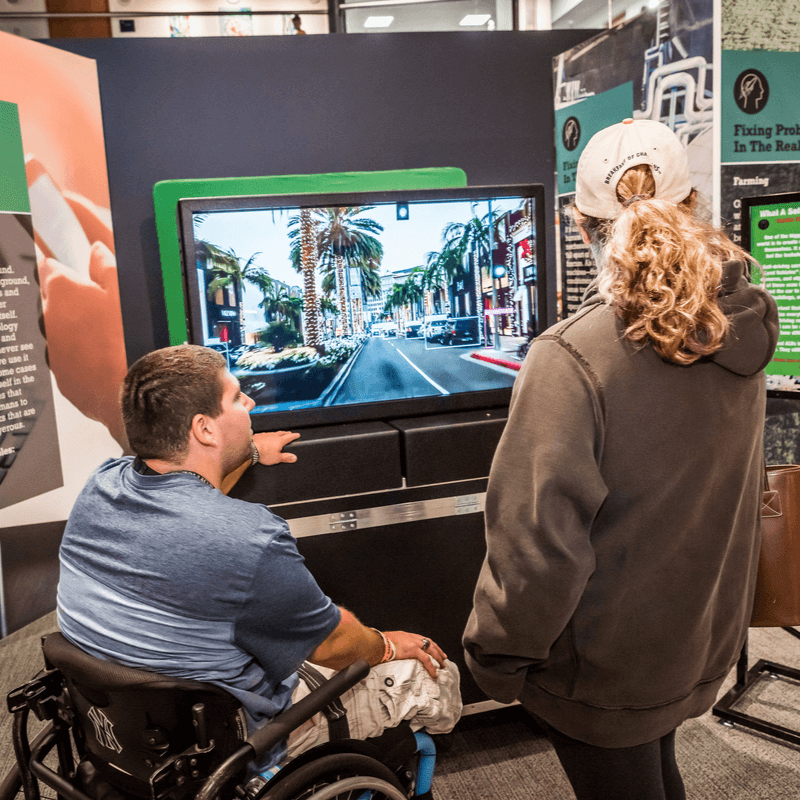 A man in a wheelchair and a blonde-haired woman looking at a TV