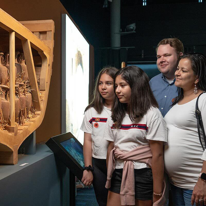 Family group looking at wooden craftworks in Pompeii exhibit.