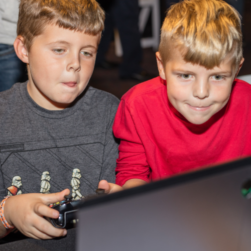 Two young boys playing a video game at Otronicon