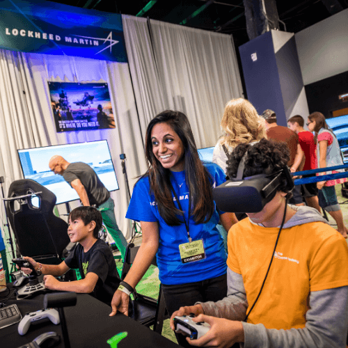 Otronicon exhibitor helping attendee work a virtual reality exhibit