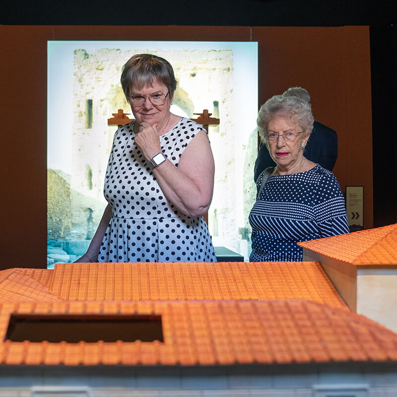 Two older adults examining a scale model of Pompeii city dwelling.