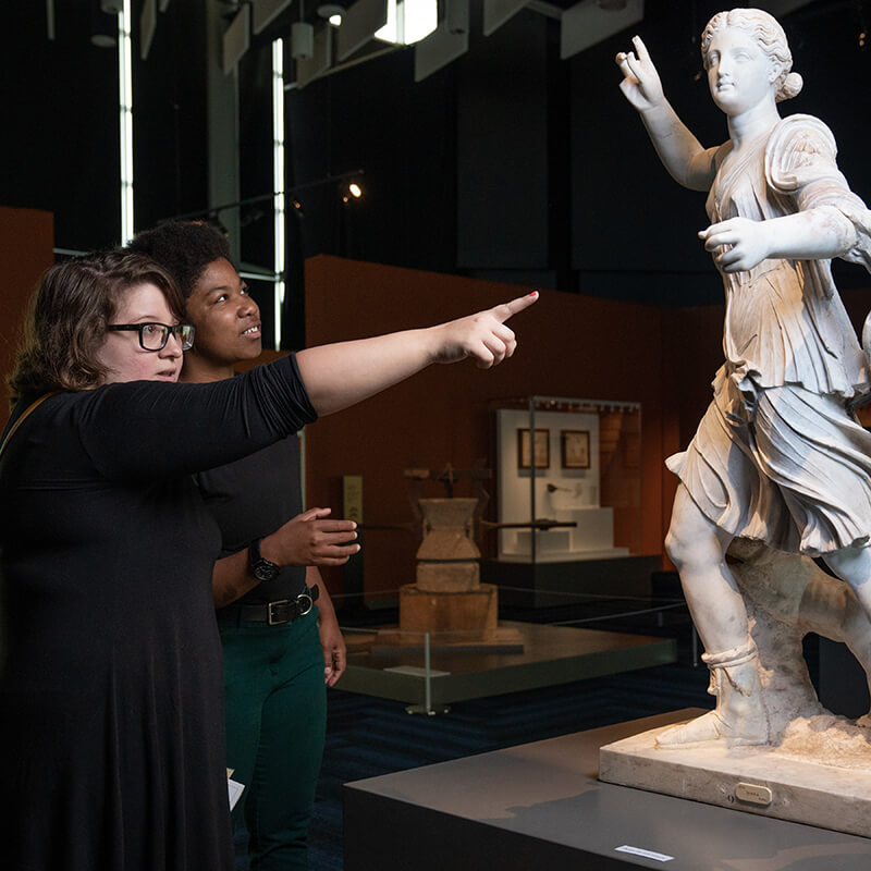 Two young adults pointing at a Pompeii era statue.