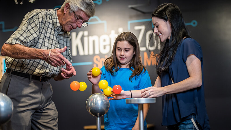 A family balancing plastic balls in the air with the air resistance exhibit.